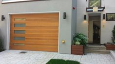 Modern garage door design.  Who says the windows need to be at the top of the door?  Power it with a #Chamberlain.