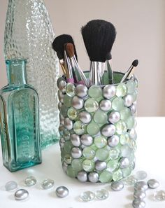 Take a soup can, paint it your favorite color, and hot glue marbles on the outside