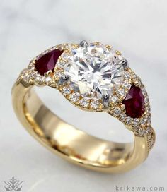 Bring the past to the present with this gorgeous engagement ring. The delicate yet elegant opening under the center stone gives the ring that vintage feel along with the pave band. Choose your center and two side stones to make it your one-of-a-kind engagement ring! Pictured here in 18k yellow gold, a diamond center stone and ruby accents. Design your Vintage Old World Engagement Ring today!