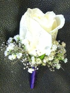 White full size rose boutonniere with fresh babys breath, silver glitter gyp and stem wrapped in royal blue