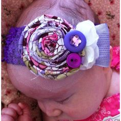 Rolled fabric flower, button & jewel topping with a bit of tulle on a clip. I glued some felt on the underside of the crocheted headband to protect delicate baby skin from the clip scratching or indenting. :)