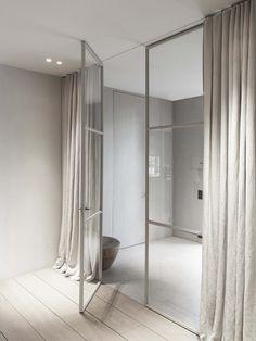porta de vidro com estrutura de metal no tom das cortinas e piso