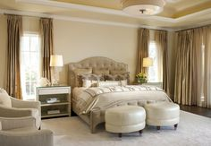 This elegant master bedroom has a very soft, neutral color palette. The golden curtains are the darkest color. A pair of soft, white ottomans sit at the foot of the bed.