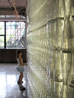 She's intrigued.  Clear glass bottle wall with just dots of clear silicone caulk for matrix.