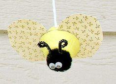 Egg Carton Bug-mobile made from cardboard egg carton, patterned paper, pom poms, google eyes and black pipe cleaner.
