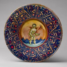 Maiolica influenced decoration on the tourney shield?    Bowl with a putto holding a pinwheel, ca. 1530  Workshop of Maestro Giorgio Andreoli (Italian, Gubbio, ca. 1465–1553)  Tin-glazed earthenware (maiolica)    Diam. 9 15/16 in. (25.2 cm)  Robert Lehman Collection, 1975 (1975.1.1107)  On view: Gallery 950   Last Updated April 26, 2012    This small lustered bowl is typical of ceramics made in Gubbio in the 1520s and 1530s.