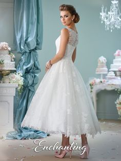Enchanting by Mon Cheri - 116136 - Sleeveless tea-length lace over tulle A-line dress with lace illusion bateau neckline, lace illusion back with covered buttons, natural waist belt with center bow, full skirt with scalloped hem.  Sizes: 0 – 20  Colors: Ivory, White