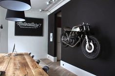 Motorcycle wall mount, matte black painted wall, wood table