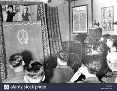 """Soldiers are pictured during a Kasperle puppet theater performance as troop entertainment on the Eastern Front, published on 10 July 1943. The Nazi Propaganda! on the back of the image reads: """"Kasperle puppet theater in the soldiers' quarter. With great joy, our mountain infrantry men on the Arctic Sea Front attend the performance."""" Photo. Berliner Verlag/Archiv Stock Photo"""