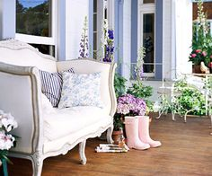 French Front Porch   An upholstered French loveseat beckons guests to linger on this cottage front porch, which overflows with containers of foxglove and delphinium.
