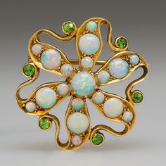 Victorian Opal & Garnet Brooch Pin Pendant 18K Gold - circa 1880. The 18k yellow gold floral motif brooch is set with crystal opals that show great fire and accented with green demantoid garnets. The brooch is light and delicate with openwork.