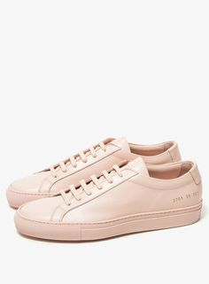 From Woman by Common Projects, a classic leather lace-up low top sneaker in Blush. Featuring a round toe, an allover Italian leather body, leather lining, padded ankle, gold heat pressed serial number detail on heel, rubber sole and extra matching laces.