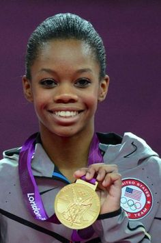 US gymnast Gabrielle Douglas poses on the podium with her gold medal after winning the artistic gymnastics women's individual all-around