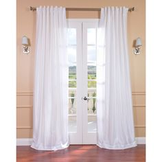 Flowy white window panels give your living room a feminine, elegant look. These snow-colored panels drape gracefully from the curtain rod, cascading into a pile of luxurious beauty on your floor. Cut utility costs with these beautiful curtains.