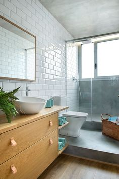 In this modern bathroom, white subway tiles line the wall and brighten up the bathroom. A glass shower screen allows the natural light from the window to pass through to the rest of the bathroom.