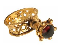 .:. Byzantine gold and garnet ring with openwork hoop, c. 6th-7th century CE.