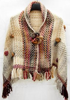 capa con aplicaciones en flamé de lana y lana hilada a mano, broche incluido