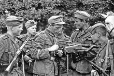 Soldiers of the Russian Liberation People's Army, a Nazi collaborationist organization, get tactical instructions from a German NCO (wearing German army cap), August 1943.  Formed in occupied Belarus by two White emigres, S.V. Ivanov and Constantine Kromiadi, RONA fought alongside the Waffen SS. Eventually, the Germans suspected RONA of collaborating with Soviet partisans as well and dissolved the unit.