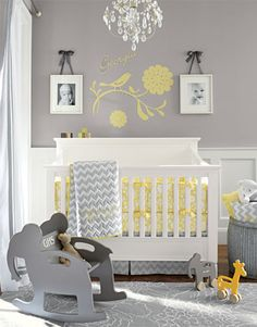 Girls Nursery- Versatile gray gets a cheery lift from vivid yellow in this nursery. Classic florals are paired with an energetic chevron pattern, and a chandelier accented with crystals adds whimsical appeal. We chose a pair of black-and-white photos to flank the decorative wall stencil and a rug with an oversized white-on-gray floral pattern in keeping with the theme.