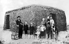 A homesteading family stands proudly with all of their possessions, in this case three chairs, in front of their sod house, near Rock Lake, North Dakota, in 1905.    It was customary for people to take all of their possessions out in front of their home whenever a traveling photographer came around. Children were also outfitted in their Sunday best, which did not necessarily include shoes, as they were considered to be a great luxury during this time.