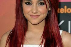 Ariana Gre mit grellroten glänzenden Haaren mit freifallenden kurzen Seitensträhnen, schwarze Augen geschminkt mit schwarzem Augenstift und schwarzer Wimperntusche, Ariana Gre mit weißem Top mit dünnen Trägern auf dem roten Teppich
