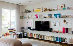 Os objetos parecem flutuar sobre as paredes da sala projetada pelo arquiteto Gustavo Calazans. O segredo são as finíssimas chapas de aço, que suportam bastante peso – inclusive a TV. Repare que os livros, na base, foram organizados por cor