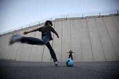 Cambiare il senso di un muro. (Bambini palestinesi giocano a calcio davanti al muro di separazione con Israele, ad Abu Dis, West Bank, sobborgo di Gerusalemme) Ph. Ahmad Gharabli