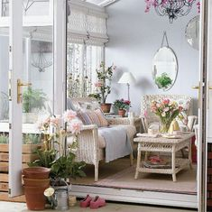 Surrounded by flowers and open airy windows this sun room has an awesome setting. The wicker sofa set and french provencal detailing are so appealing. It is so welcoming and absolutely charming!