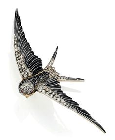 A late 19th century enamel, diamond and ruby bird brooch.   Modelled as a swallow in flight, applied with black enamel, to the old and rose-cut diamond wing borders, tail and head, with ruby eyes, circa 1890,