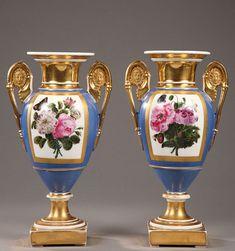 Une paire de vases en porcelaine de Paris sur socle carré avec des anses intégralement dorées, ornées de médaillons antiques à têtes de femmes. Sur fond bleu, des larges cartouches...