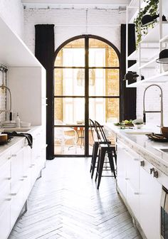 arched black framed windows leading to outdoor patio. / sfgirlbybay