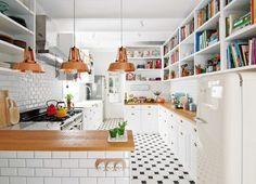 Cocina moderna en blanco, madera y cobre, con azulejos tipo subway y piso de calcáreos en blanco y negro. En una casa a puro blanco con acentos de color.