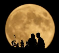 A couple sits on a bluff overlooking the Missouri River as the full moon rises in the distance in Kansas City, USA. Monday night's full moon was the third and final 'supermoon' of 2014. The phenomenon, which scientists call a 'perigee moon,' occurs when the moon is near the horizon and appears larger and brighter than other full moons. Picture: Charlie Riedel/AP