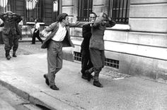 25 August 1944: 'Paris broken! Paris martyred! But Paris liberated!' Brimming with anger, a French man attacks a German soldier being marched through the streets of Paris following his capture by members of the French Resistance.Paris, Île-de-France, France. 25 August 1944. Image taken by Robert Capa.