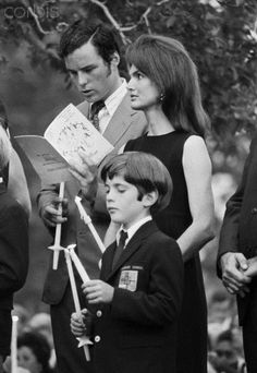 Jacqueline Kennedy Onassis with JFK Jr. and half-brother Jamie Auchincloss, at RFK Mass in Arlington Cemetery, June 6, 1969.