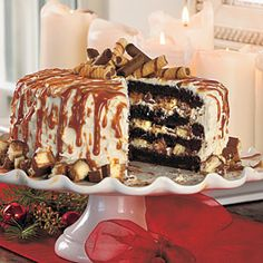 Decadent Cheesecake-Stuffed Dark Chocolate Cake Recipe Devils food cake layered with cheesecake bites and candy bars all topped with cream cheese frosting drenched with dulce de leche caramel sauce and chocolate cookies!