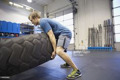 Stock Photo : Man doing tire-flip exercise in Gym gym