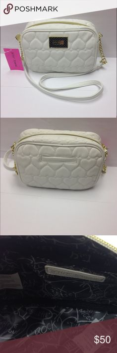 "New Betsey Johnson Camera Crossbody bag 100% New with Tags Betsey Johnson white crossbody with quilted hearts.             EXTERIOR: *  White quilted hearts,polyurethane body  *  Rear slip pocket *  Strap in White/Gold         *  Black & Gold logo hardware plate *  Gold tone hardware *  Platform bottom *  Full zipper closure  INTERIOR: *  Side wall zipper compartment *  Signature black/silver lining  Approx. Measurements: 6.5""(h)  x 9.5""(L) x 3 1/2"" (d) Strap - 22"" Betsey Johnson Bags…"
