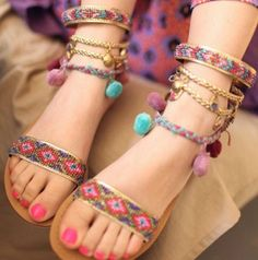 Lovely boho sandals. Love the gold braid and embroidered ankle straps with cute pom poms!