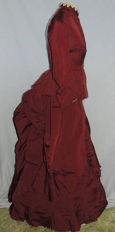 This beautiful 1870's bustle dress is made from a cranberry silk faille. The bodice is lined in a window pane tan cotton and bones in the seams. It hooks down the side front under the pleats, there are 3/4 length sleeves with box plests between flaps and a knotted bow, underneath is ivory lace. The jacket is piped in a plum silk piping. It has a high collar trimmed with lace and a beautiful mother of pearl leaf hook at the waist.