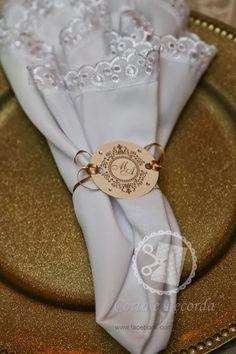 Porta guardanapos em papel perolado gramatura 250 g/m², detalhe em fita de cetim dourada e 4 strass de 3mm.