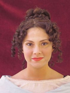 A good example of what hair looked like during the regency period. Tight curls worn over the head and ears with the rest of the hair up into a loose bun or Psyche knot.