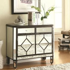 This stunning Mirrored Accent Cabinet has a chic appeal. The mirrored panels are framed with a brown trim and a diamond detail on each door.