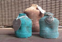 Oude vazen ingesmeerd met muurvuller van de action, daarna geverfd met kinderverf van de action ( geel en blauw gemengd) en toen bijna alles droog was nog ingesmeerd met zand!