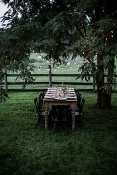 beautiful country setting....love the old timber table, the lights trees, fence.....everything.......