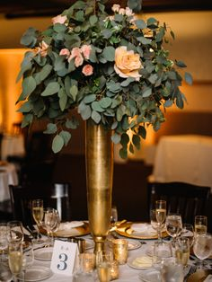 Elevated centerpiece with eucalyptus and roses in tall gold vase. More