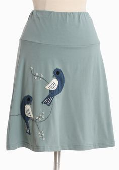 """Birds On A Line Skirt By Synergy 52.99 at shopruche.com. This classic A-line skirt by Synergy is crafted in a soft organic cotton blend and blue green hue. Finished with charming embroidery, top stitched appliquès, and an elasticized waist for a comfortable fit.95% Organic cotton, 5 % Lycra, Imported, 19.5"""" length from top of waist"""