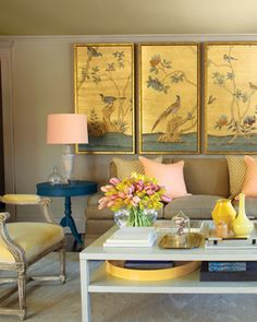 Superneutrals  This soft and striking living room is anchored in neutral tan shades, but the peach lampshades, yellow accents, and blue end tables add modern pop to the space.