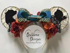 Bring a little magic into your life with these mouse ears inspired by the mother-daughter story of Disneys Brave. Wire ears crafted out of white lace, gold paint details, artificial rose and orange hydrangea flowers, gold arrow, greenish-blue and gold ribbon, modeled black bear