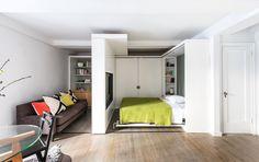 Wanneer het bed opgeklapt is tegen de wand en de bewegende wand de slaapkamer 'sluit', kun je de andere ruimte betrekken bij de woonkamer. Zo komt er zelfs nog een werkruimte tevoorschijn zodra je de kastdelen aan de andere kant open schuift.